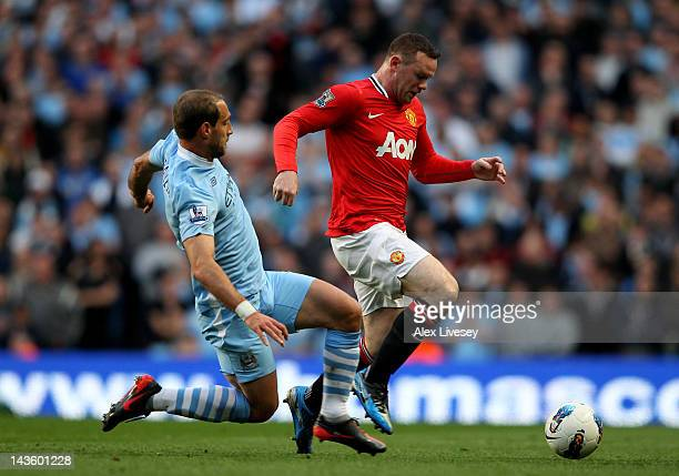 Wayne Rooney of Manchester United is challenged by Pablo Zabaleta of Manchester City during the Barclays Premier League match between Manchester City...