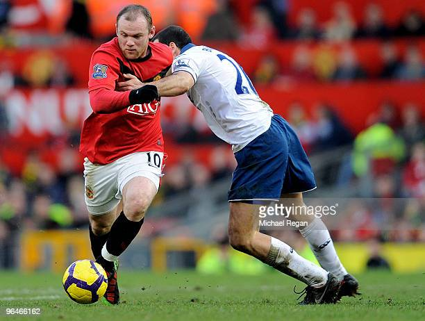 Wayne Rooney of Manchester United is challenged by Tal Ben Haim of Portsmouth during the Barclays Premier League match between Manchester United and...