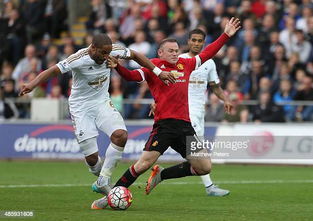 Wayne Rooney of Manchester United is tackled by Ashley Williams of Swansea City but no penalty is given during the Barclays Premier League match...