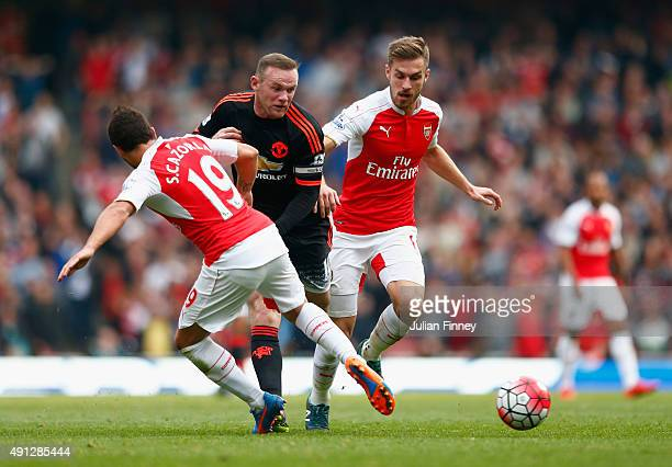 Wayne Rooney of Manchester United is tackled by Santi Cazorla and Aaron Ramsey of Arsenal during the Barclays Premier League match between Arsenal...