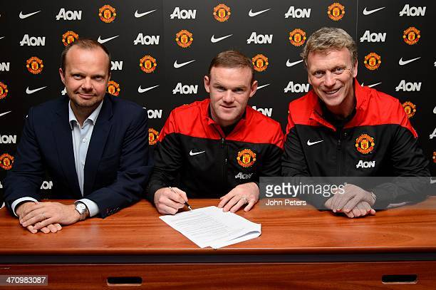 Wayne Rooney of Manchester United poses with Manager David Moyes and Executive Vice Chairman Ed Woodward after signing a contract extension at...