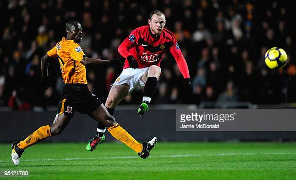 Wayne Rooney of Manchester United shoots at goal under pressure from George Boateng of Hull City during the Barclays Premier League match between...