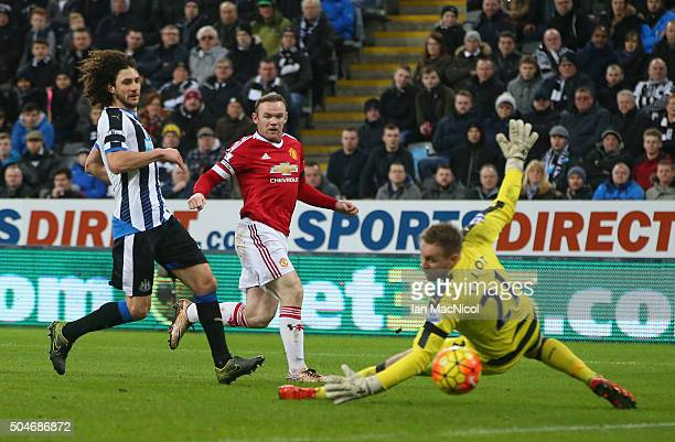 Wayne Rooney of Manchester United shoots wide as goalkeeper Robert Elliot of Newcastle United dives for the ball during the Barclays Premier League...
