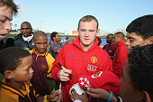 Wayne Rooney of Manchester United signs autographs during a visit to a provincial government coaching clinic in Kyelitsha during their preseason tour...