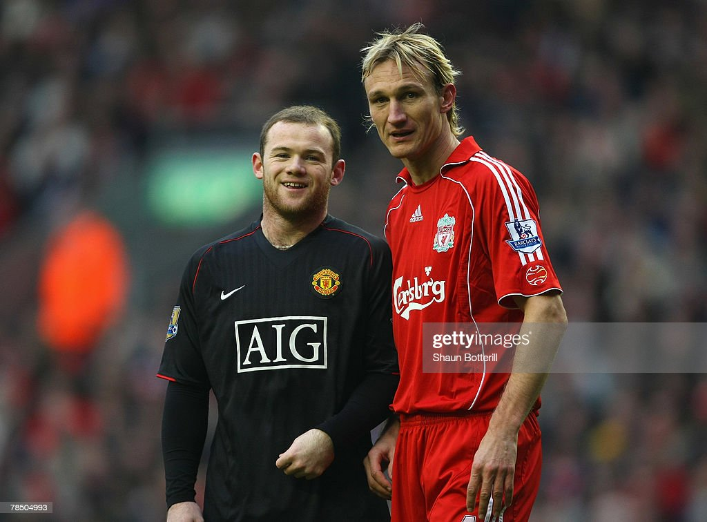 Wayne Rooney of Manchester United smiles as Sami Hyypia of Liverpool looks on during the Barclays Premier League match between Liverpool and...