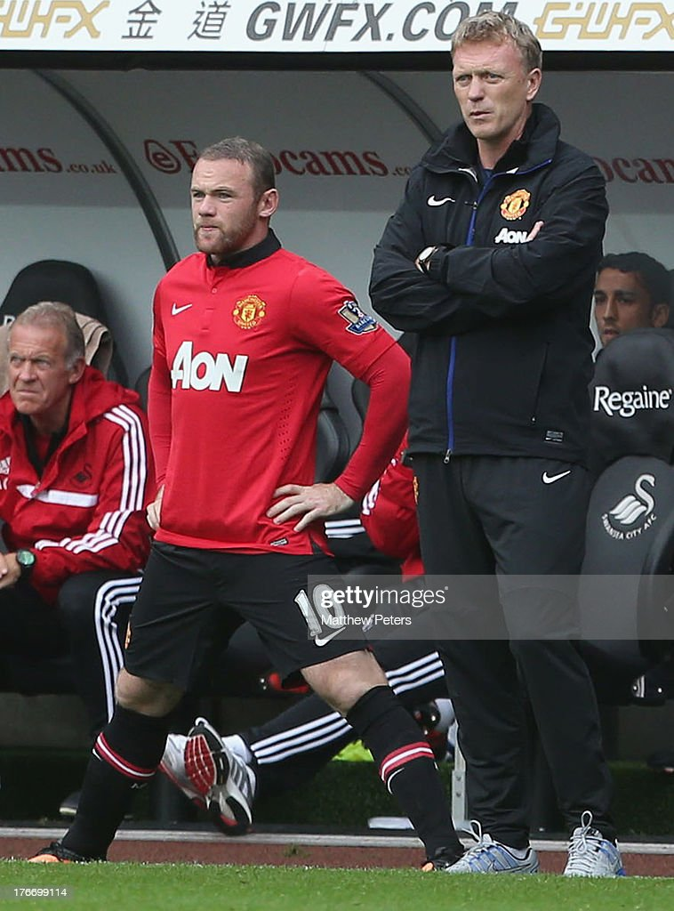 <a gi-track='captionPersonalityLinkClicked' href=/galleries/search?phrase=Wayne+Rooney&family=editorial&specificpeople=157598 ng-click='$event.stopPropagation()'>Wayne Rooney</a> of Manchester United stands next to Manager <a gi-track='captionPersonalityLinkClicked' href=/galleries/search?phrase=David+Moyes&family=editorial&specificpeople=215482 ng-click='$event.stopPropagation()'>David Moyes</a> as he prepares to come on as a substitute during the Barclays Premier League match between Swansea City and Manchester United at the Liberty Stadium on August 17, 2013 in Swansea, Wales.