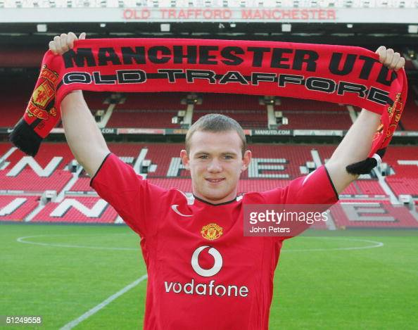 Wayne Rooney poses for photographs with a Manchester United shirt and scarf after signing for Manchester United on August 31 2004 at Old Trafford in...