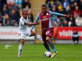 Wayne Routledge of Swansea City battles with Ryan Bertrand of Aston Villa during the Barclays Premier League match between Swansea City and Aston...