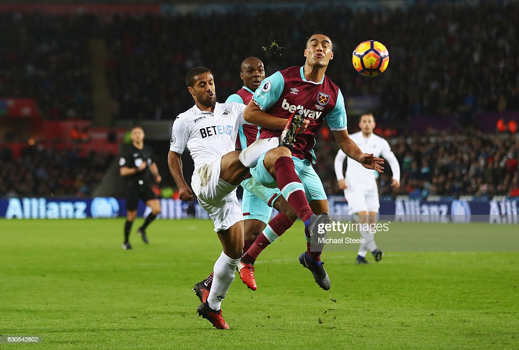 Wayne Routledge of Swansea City challenges for the ball with Winston Reid of West Ham United during the Premier League match between Swansea City and West Ham United at Liberty Stadium on December 26, 2016 in Swansea, Wales.