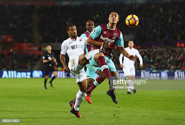 Wayne Routledge of Swansea City challenges for the ball with Winston Reid of West Ham United during the Premier League match between Swansea City and...
