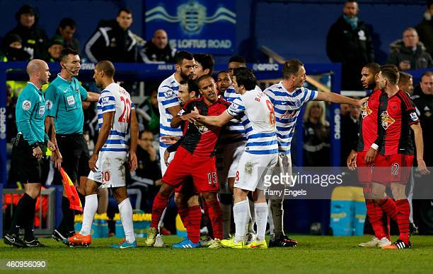 Wayne Routledge of Swansea City clashes with Joey Barton of QPR after fouling Karl Henry of QPR during the Barclays Premier League match between...