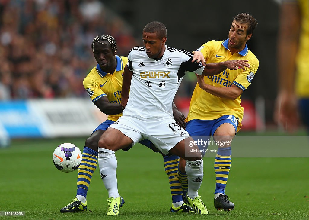 <a gi-track='captionPersonalityLinkClicked' href=/galleries/search?phrase=Wayne+Routledge&family=editorial&specificpeople=206672 ng-click='$event.stopPropagation()'>Wayne Routledge</a> (C) of Swansea City is crowded out by <a gi-track='captionPersonalityLinkClicked' href=/galleries/search?phrase=Bacary+Sagna&family=editorial&specificpeople=745680 ng-click='$event.stopPropagation()'>Bacary Sagna</a> (L) and <a gi-track='captionPersonalityLinkClicked' href=/galleries/search?phrase=Mathieu+Flamini&family=editorial&specificpeople=242961 ng-click='$event.stopPropagation()'>Mathieu Flamini</a> (R) of Arsenal during the Barclays Premier League match between Swansea City and Arsenal at the Liberty Stadium on September 28, 2013 in Swansea, Wales.