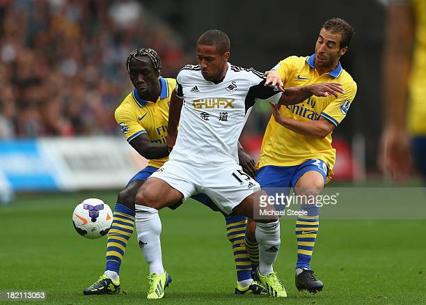 Wayne Routledge of Swansea City is crowded out by Bacary Sagna and Mathieu Flamini of Arsenal during the Barclays Premier League match between...