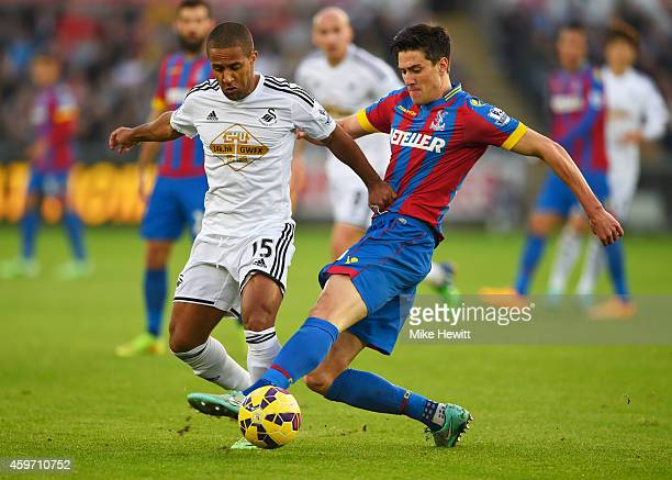Wayne Routledge of Swansea City is tackled by Martin Kelly of Crystal Palace during the Barclays Premier League match between Swansea City and...
