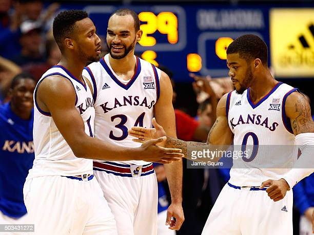 Wayne Selden Jr #1 of the Kansas Jayhawks is congratulated by Perry Ellis and Frank Mason III after making a threepointer and drawing a foul during...