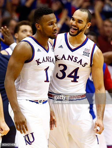 Wayne Selden Jr #1 of the Kansas Jayhawks is congratulated by Perry Ellis after making a threepointer and drawing a foul during the second overtime...