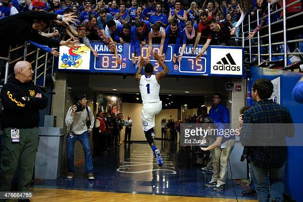 Wayne Selden Jr #1 of the Kansas Jayhawks slaps the hanks of fans after a win against the Oklahoma Sooners at Allen Fieldhouse on February 24 2014 in...