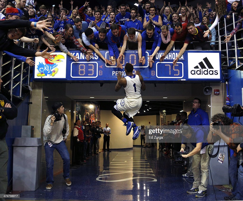 Wayne Selden Jr #1 of the Kansas Jayhawks slaps the scoreboard and celebrates with fans after a 8375 win over the Oklahoma Sooners at Allen...