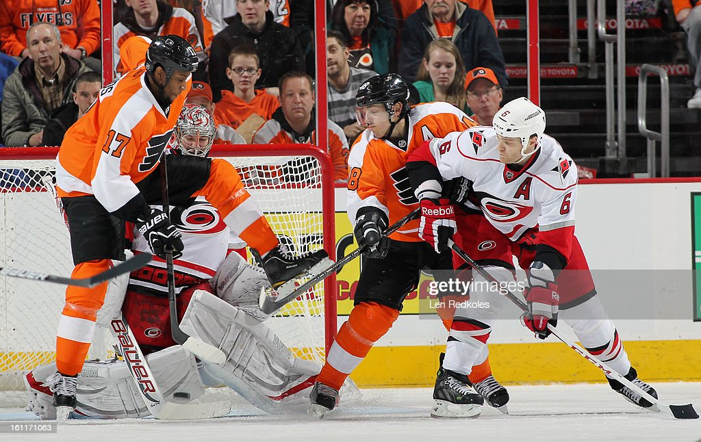 Wayne Simmonds #17 and Danny Briere #48 of the Philadelphia Flyers battle with Tim Gleason #6 of the Carolina Hurricanes in front of goaltender Cam Ward #30 on February 9, 2013 at the Wells Fargo Center in Philadelphia, Pennsylvania.