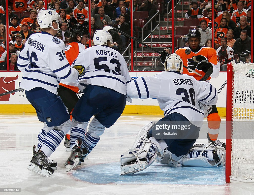 Wayne Simmonds #17 of the Philadelphia Flyers attempts to play the puck out of mid-air against Carl Gunnarsson #36, Michael Kostka #53 and goaltender Ben Scrivens #30 of the Toronto Maple Leafs on February 25, 2013 at the Wells Fargo Center in Philadelphia, Pennsylvania. The Maple Leafs went on to defeat the Flyers 4-2.