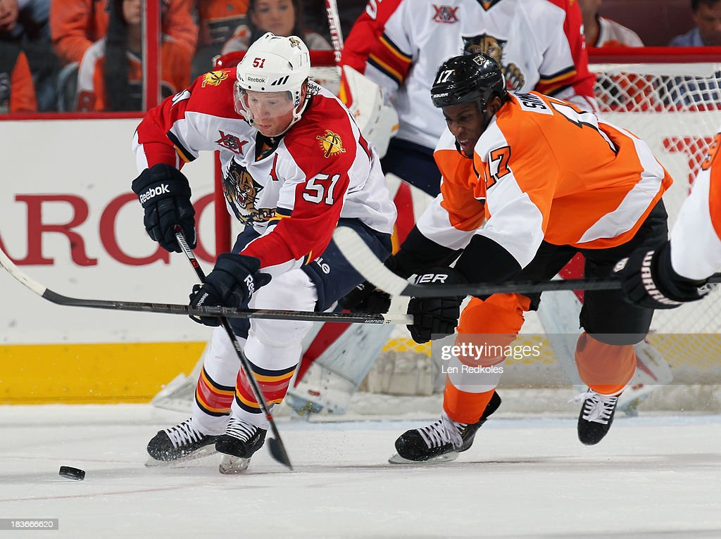 Wayne Simmonds #17 of the Philadelphia Flyers battles for control of the loose puck with Brian Campbell #51 of the Florida Panthers on October 8, 2013 at the Wells Fargo Center in Philadelphia, Pennsylvania.