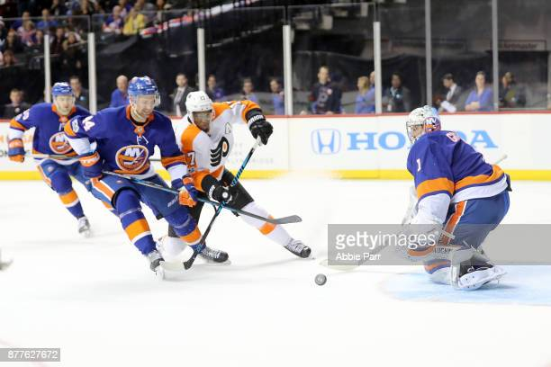 Wayne Simmonds of the Philadelphia Flyers chases for the puck against Thomas Hickey and Thomas Greiss of the New York Islanders in the third period...