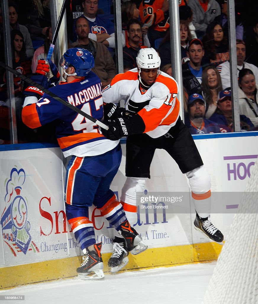 Wayne Simmonds #17 of the Philadelphia Flyers checks Andrew MacDonald #47 of the New York Islanders into the boards during the first period at the Nassau Veterans Memorial Coliseum on October 26, 2013 in Uniondale, New York.