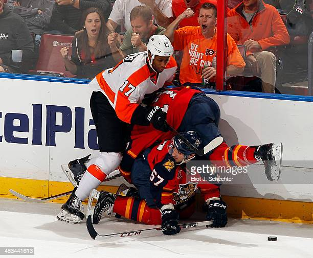 Wayne Simmonds of the Philadelphia Flyers collides with Vincent Trocheck and Colby Robak of the Florida Panthers at the BBT Center on April 8 2014 in...