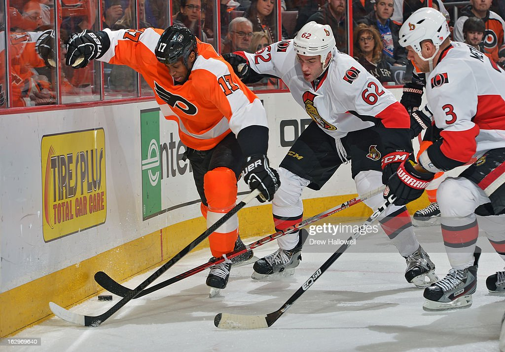 Wayne Simmonds #17 of the Philadelphia Flyers fights for the puck against Eric Gryba #62 and Marc Methot #3 of the Ottawa Senators at the Wells Fargo Center on March 2, 2013 in Philadelphia, Pennsylvania.