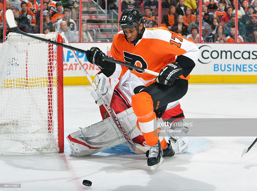 Wayne Simmonds #17 of the Philadelphia Flyers fights past Cam Ward #30 of the Carolina Hurricanes to get to the puck at the Wells Fargo Center on February 9, 2013 in Philadelphia, Pennsylvania.