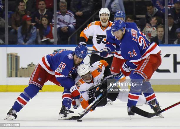 Wayne Simmonds of the Philadelphia Flyers goes up against Tanner Glass and Oscar Lindberg of the New York Rangers at Madison Square Garden on April 2...