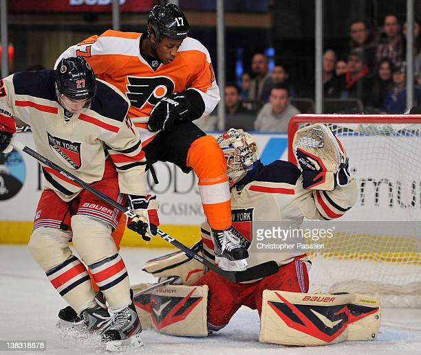 Wayne Simmonds of the Philadelphia Flyers leaps in the air in front of Henrik Lundqvist of the New York Rangers as he attempts to deflect a shot on...