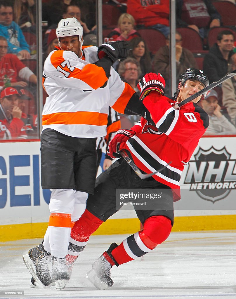 Wayne Simmonds #17 of the Philadelphia Flyers sends Dainius Zubrus #8 of the New Jersey Devils to the ice on this check during the third period of an NHL hockey game at Prudential Center on November 2, 2013 in Newark, New Jersey.