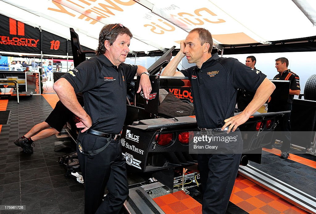 Wayne Taylor (L) of South Africa and Max Angelelli of Italy talk in the paddock before the VisitFlorida.com Sports Car 250 at Road America on August 10, 2013 in Elkhart Lake, Wisconsin.