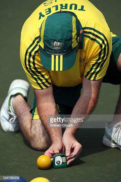 Wayne Turley of Australia concentrates intently as he measures a bowl during the Mens Triples lawn bowls game against host nation India at JN Sports...