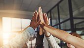 Shot of a group of colleagues giving each other a high five