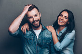 Studio shot of beautiful young couple in jeans wear standing close to each other and looking at camera with smile