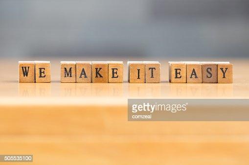 Temos de tornar mais fácil. palavra escrita em um bloco de madeira : Foto de stock
