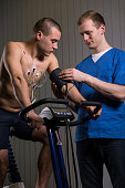 Sportsman on exercise bike and medic checking his blood pressure