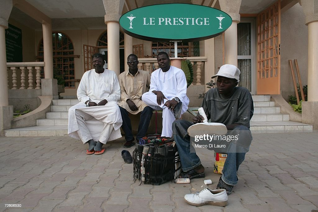 N'DJAMENA CHAD NOVEMBER 3 Wealthy Chadian men sit in front of a restaurant waiting to have their shoes clean on November 3 2006 in N'Djamena Chad...