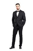 Wealthy confident relaxed young man in tuxedo looking at camera with hands in pockets. Full body length portrait isolated over white studio background