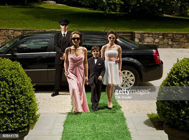 Wealthy family arriving for black tie event.