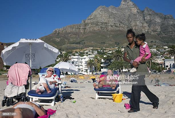 Wealthy tourists enjoy the beach as the sun sets on March 20 2009 in Camps Bay a posh sea side resort in Cape Town South Africa Camps Bay is one of...