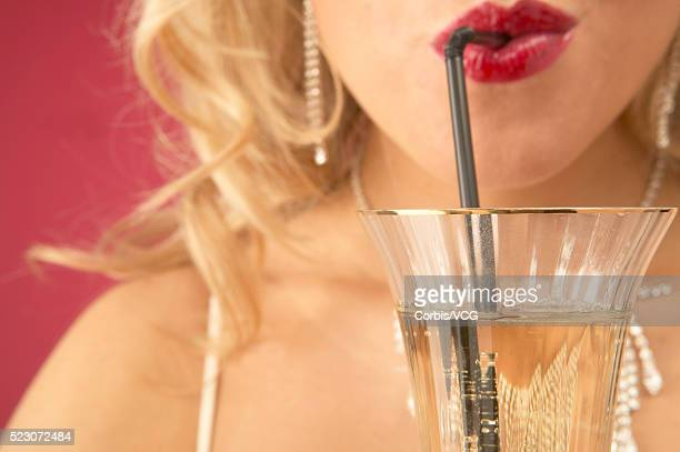 Wealthy Young Woman Drinking Champagne Through Straw