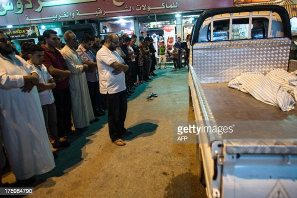 A weapon lies on the ground as Syrian men pray on the street next to a truck carrying the bodies of six members of the same family killed in a bomb...