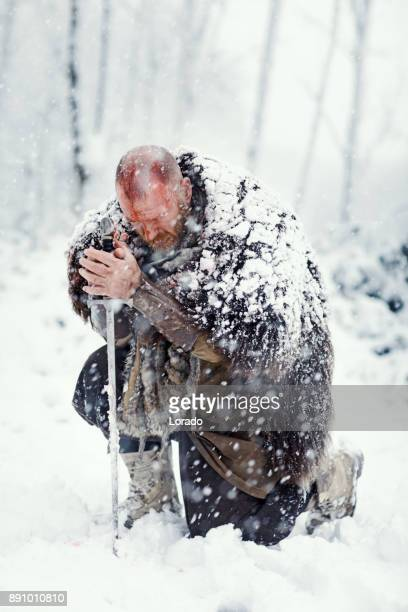 Waffe schwingende blutigen Wikinger-Krieger im Freien in einem Schneesturm winter