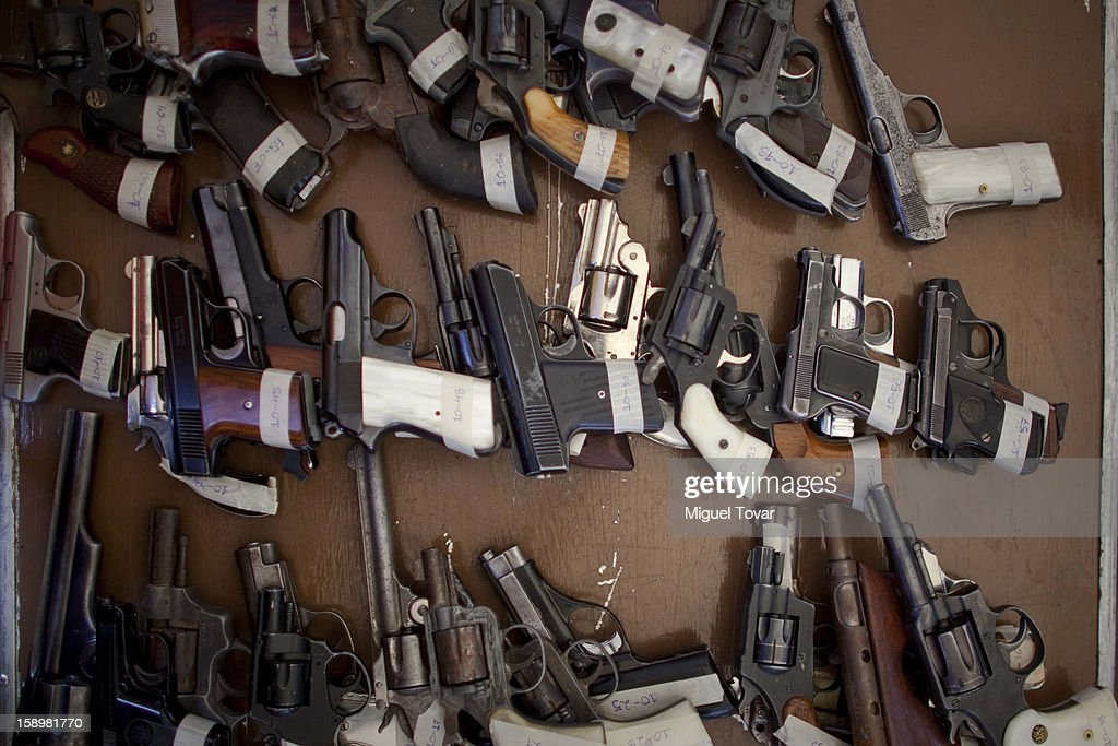 Weapons are lined up on a table by mexican soldiers, after being exchanged by their owners on January 04, 2013 in Mexico City, Mexico. More than a thousand weapons have been changed for a tablet, bicycles or money in a low-income neighborhood in the capital, according to authorities.