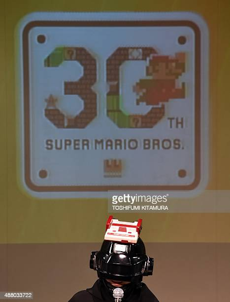 Wearing a helmet with a Nintendo family computer Japanese musician Sakamoto Kyoju or 'professor Sakamoto' speaks during a live performance of the...