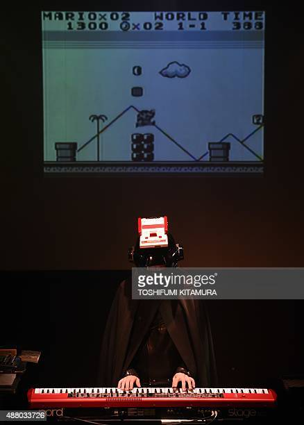 Wearing a helmet with a Nintendo family computer Japanese musician Sakamoto Kyoju or 'professor Sakamoto' performs during a live performance of the...