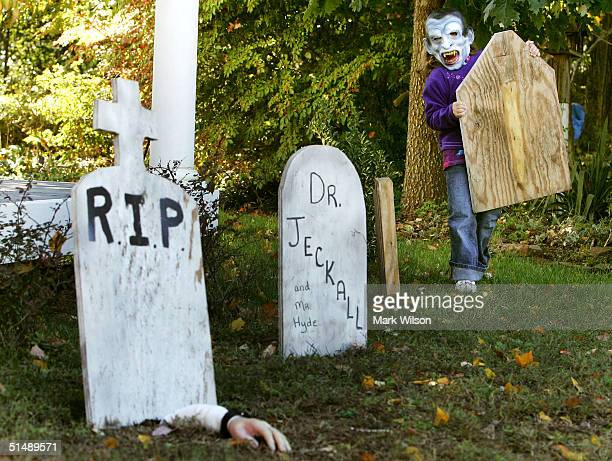 Wearing a mask Kyndra Hendrick 6yearsold helps her parents by setting up fake gravestones in front of her house October 17 2004 in Owings Maryland...